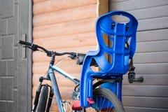 Fiets met kinderen die zetel dragen in bijlage Cyclus met het materiaaltribune van het jonge geitjesvervoer dichtbij houten garag stock foto's