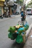 Fiets met kruidenierswinkels en gomlaarzen wordt geladen op bovenkant die Vietnam stre Stock Fotografie