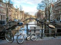 Fiets op de brug en de bezinning van gebouwen van de duch traditionele Vlaamse baksteen van Amsterdam de beroemde op het kanaal royalty-vrije stock fotografie