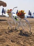 Fiets op een strand naast de paraplu's wordt geparkeerd die Stock Afbeelding