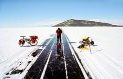 Fiets op het ijs van Baikal, een gang met een fiets door de winter Baikal stock afbeelding