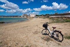 Fiets op zandig strand wordt geparkeerd dat Royalty-vrije Stock Afbeelding