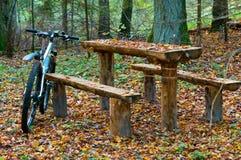 Fiets rond een houten lijst met banken in het hout Stock Fotografie