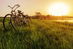 Fiets twee dichtbij de achtergrond van de meerzonsondergang Twee uitstekende fietsen bij zonsondergang Het concept Romaans en lie stock afbeelding