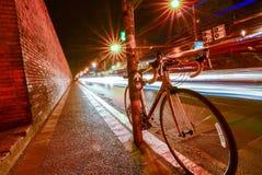 Fietsen in de straat met lichten bij nacht worden geparkeerd die Stock Foto's