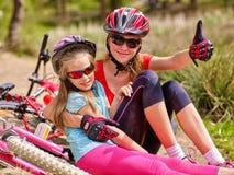 Fietsen die familie cirkelen De gelukkige moeder en de dochter zitten op weg dichtbij fietsen royalty-vrije stock afbeeldingen