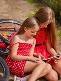 Fietsen die meisje cirkelen in park De kinderen letten tablet op PC Royalty-vrije Stock Fotografie