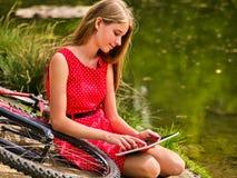 Fietsen die meisje cirkelen in park De kinderen letten tablet op PC Stock Afbeelding