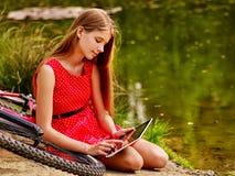 Fietsen die meisje cirkelen in park De kinderen letten tablet op PC Royalty-vrije Stock Foto