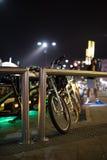 Fietsen in een fietsenrek in nacht diecityscape wordt geplaatst Stock Foto