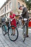 Fietsen en jonge mannen en vrouw gekleed in ouderwetse tweed Royalty-vrije Stock Foto's