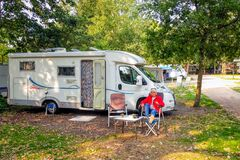 Enjoy a nice autumn sun next to the camper at a campsite.