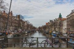 Fietsen op brug met mening van kanaal en gebouwen van Amsterdam van de binnenstad stock foto's