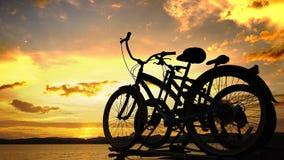 Fietsen op zonsondergangachtergrond stock foto's