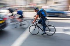Fietser in de stadsverkeer van Londen in motieonduidelijk beeld stock afbeelding
