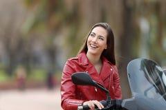 Fietser die het bekijken kant op haar motor denken royalty-vrije stock fotografie