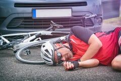 Fietser die op de weg na het raken door een auto liggen Stock Foto's