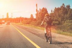 Fietser die op fiets op de weg van het plattelandsasfalt met autoverkeer berijden stock fotografie