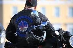 Fietser in een versterkt vest met het embleem van de Impuls van de motorclub van Weg, achtermening royalty-vrije stock foto