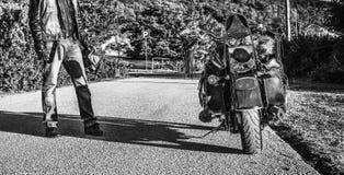 Fietser en klassieke motorfiets bij zonsondergang in zwart-wit stock fotografie
