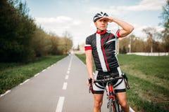Fietser in helm en sportkleding op sportfiets stock afbeelding