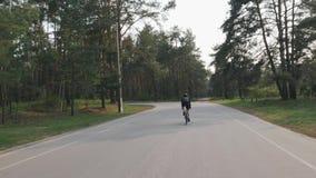 Fietser het berijden alleen in het park terwijl opleiding voor ras De rug volgt schot van fiets van de fietser de pedaling weg La stock videobeelden