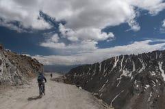 Fietser het berijden in Khardungla-Pas op Road van Leh Nubra stock foto
