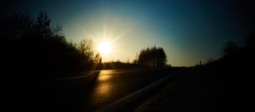 Fietser het berijden onderaan de straat in de gloed van de het plaatsen zon stock foto
