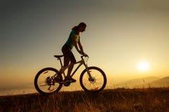 Fietser-meisje bij de zonsondergang Stock Afbeelding