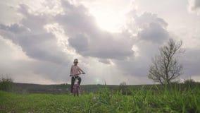 Fietser-meisje bij de zonsondergang op de weide Kind die van vrijheid op fiets op tarwegebied genieten bij zonsondergang Meisje o stock video