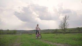Fietser-meisje bij de zonsondergang op de weide Kind die van vrijheid op fiets op tarwegebied genieten bij zonsondergang Meisje o stock footage