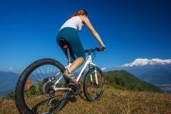 Fietser-meisje in de bergen van Himalayagebergte Royalty-vrije Stock Foto