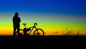 Fietser met fietssilhouet tegen zonsondergang Royalty-vrije Stock Foto