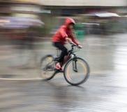 Fietser op de stadsrijweg op een regenachtige dag royalty-vrije stock afbeeldingen
