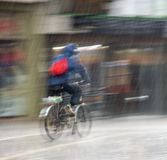 Fietser op de stadsrijweg op een regenachtige dag royalty-vrije stock afbeelding