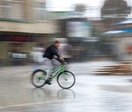Fietser op de stadsrijweg op een regenachtige dag royalty-vrije stock foto's