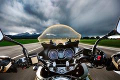 Fietser op een motorfiets die onderaan de weg in een bliksemstor daveren stock foto