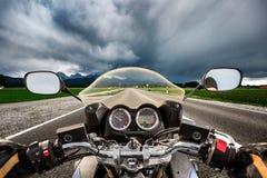 Fietser op een motorfiets die onderaan de weg in een bliksemstor daveren stock foto's