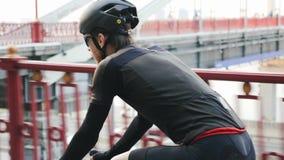Fietser op fiets met brug op de achtergrond Gemakkelijke rit op wegfiets in het stadspark r Langzame Motie stock video