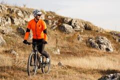 Fietser in Oranje Jasje die de Fiets berijden op Rocky Trail Extreem Sportconcept Ruimte voor tekst stock foto's