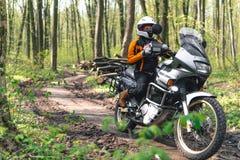 Fietsermeisje dat een motorfietsuitrusting, beschermende kleding, materiaal, avonturen toeristische motor met zijzakken draagt op stock fotografie