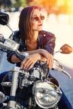 Fietsermeisje in een leerjasje op een motorfiets stock foto
