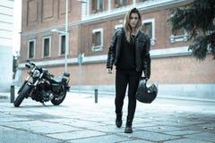 Fietsermeisje in een leerjasje op een motorfiets stock fotografie