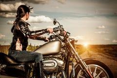 Fietsermeisje op een motorfiets stock afbeeldingen