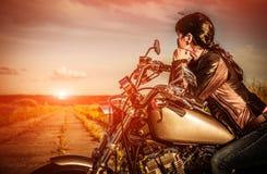 Fietsermeisje op een motorfiets Stock Foto