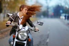 fietsermeisje op motorfiets stock foto's
