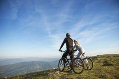 Fietserpaar met bergfietsen die zich op de heuvel onder de avondhemel bevinden en van heldere zon genieten bij de zonsondergang Stock Foto's