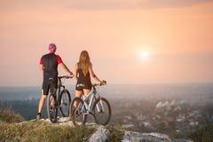 Fietserpaar met bergfietsen op de heuvel bij zonsondergang stock afbeeldingen