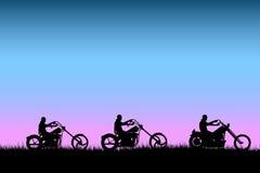 Fietsers die bij zonsondergang op de weg drijven Stock Afbeeldingen