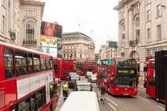Fietsers die ruimte met auto's en bussen op de straten van Londen, het UK vechten stock afbeelding